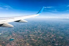 Wing of an airplane flying above the land Royalty Free Stock Image