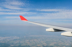 Wing of airplane flying above the land Stock Image