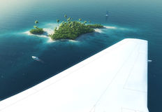 Wing of an airplane flying above paradise tropical island Royalty Free Stock Photography