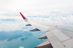 Wing of an airplane flying above sea Stock Images