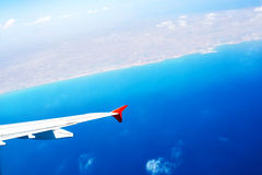 Wing of an airplane flying above the sea Royalty Free Stock Photos