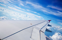 Wing of an airplane flying above the sky Stock Photos