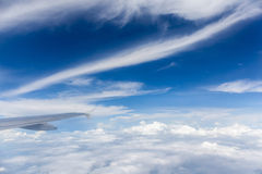 Wing of the airplane flying above the white fluffy clouds. Royalty Free Stock Photography