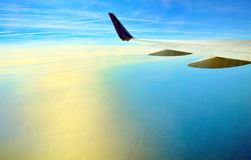 Wing of airplane flying royalty free stock photography