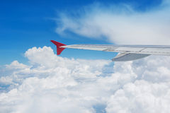 Wing of an airplane flying in the sky Stock Photos