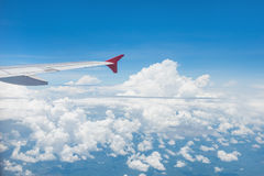 Wing of an airplane flying in the sky Royalty Free Stock Images