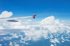 Wing of an airplane flying in the sky Royalty Free Stock Photo