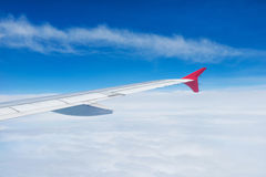 Wing of an airplane flying in the sky Royalty Free Stock Photos