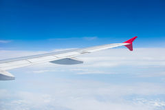 Wing of an airplane flying in the sky Stock Photo