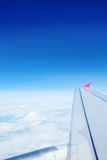 Wing of an airplane flying in the sky Stock Images