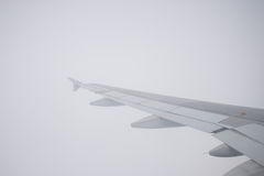 Wing of an airplane flying in the sky so Stock Photography
