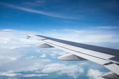 Wing of an airplane flying in the sky so Royalty Free Stock Photo
