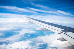Wing of an airplane flying in the sky so Stock Images