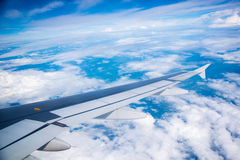 Wing of an airplane flying in the sky so Stock Image