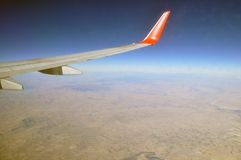 Wing of airplane flying in the sky on a clear day stock images
