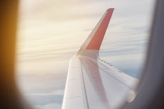 Wing of an airplane flying in sky, early morning Royalty Free Stock Image