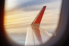 Wing of an airplane flying in sky, early morning Stock Photography