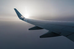 Wing of airplane and sun in fog. Wing of airplane and the sun shining through the fog of clouds Royalty Free Stock Image