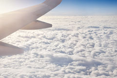Wing of an airplane with sunlight above the cloud.  Stock Photography