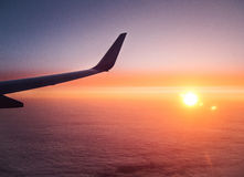 Wing of airplane at sunrise. Above the clean clouds Stock Photos