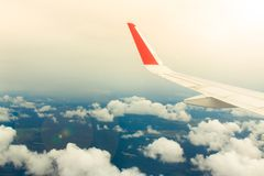 Wing of airplane from window on the background of blue sky Stock Photo