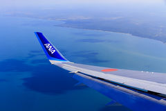 Air Travel. Theme: Airplane Wing against a Vivid Blue Sky and Ocean Stock Photography