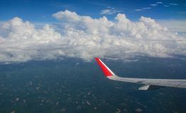Wing of civil aircraft. Airplane wing view. An aircraft flying over green fields Stock Images