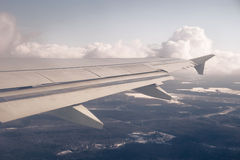 Wing and cloudscape. Clouds and sky as seen through window of aircraft Royalty Free Stock Photography