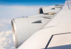 Wing with engines of Airbus A380 flying over clouds. Wing with engines of Airbus A380 airliner flying over clouds Stock Photos