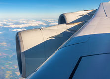 Wing with engines of Airbus A380 flying over clouds Royalty Free Stock Image