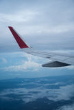Wing of flying airplain. View through the aircraft window of wing over clouds and sky background Royalty Free Stock Images