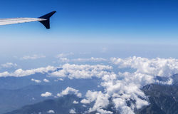 Wing of a Flying Airplane above clouds over Himalayan Mountains. India Royalty Free Stock Photo