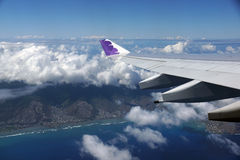 Wing of Hawaiian Airlines plane flying in the air above Honolul Royalty Free Stock Photos