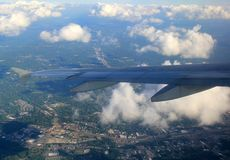 Wing of jet liner seen from window seat as it flies over buildings, puffy clouds below and beneath Royalty Free Stock Photography
