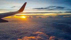 Wing of jet plane over the clouds at high altitude when sunset. Silhouette style Royalty Free Stock Image