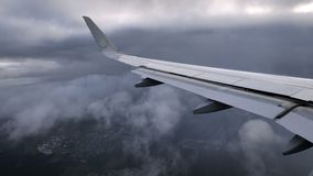 Wing of landing airplane or jet on storm gray sky background stock footage