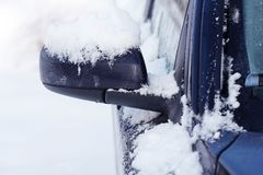 Wing mirror of car covered up with snow in winter time, close up.  Royalty Free Stock Image