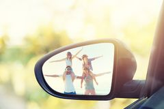 Wing mirror of a car with reflected a group of friends. At the beach royalty free stock image