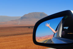 Wing Mirror Reflection in Africa. The African landscape captured from a moving car Royalty Free Stock Images