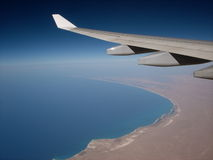Wing over Africa. This is an image of a plane wing as it's flying over the Mediterranean Ocean coming upon the Continent of Africa stock image