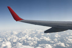 Wing over clouds. View of a public airplane wing over clouds Royalty Free Stock Photography