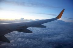 Wing passenger aircraft in flight over the evening clouds Royalty Free Stock Photos