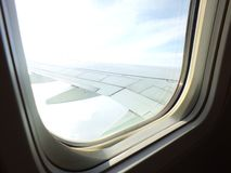 Wing passenger airplane blue sky and clouds as seen through window of an aircraft Stock Photos