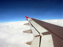 Wing of Plane. Outside plane view of wing against blue sky above the clouds stock photography