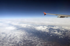 The wing of the plane above the clouds in the sky. Royalty Free Stock Photos