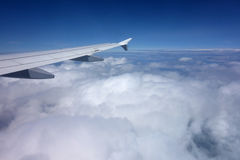 Wing of a plane above the clouds. View from a plane window Stock Photography