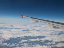 Wing. The wing of the plane on the background of clear blue sky with white clouds with the bottom Stock Images