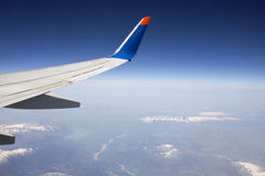 Wing of the plane on blue sky. Snowy mountains below, view from window of a jet plane wing with beautiful weather Stock Photos