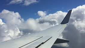 Wing of plane on blue sky with clouds background. Travel by air on airplane flight concept. Wing of plane on blue sky with clouds background. Travel by air on stock video footage