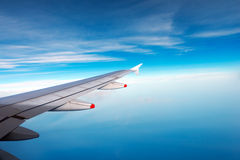 Wing of a Plane with Blue Sky and Clouds Stock Images